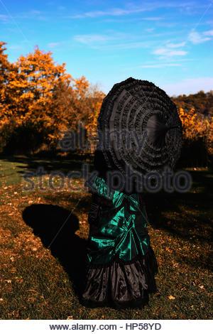 Vue arrière du Victorian woman holding an umbrella Banque D'Images