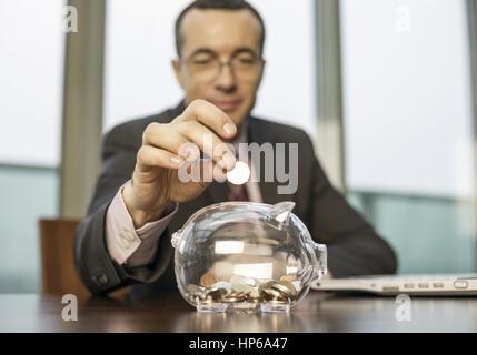 Un Muenze Mann wirft Schreibtisch dans Sparschwein (modèle récent) Banque D'Images