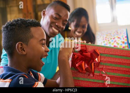 Happy black famille à la maison. African American father, mother and child celebrating birthday, s'amusant à partie. Banque D'Images