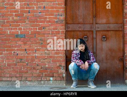 Pacific Islander woman wearing black lipsitick et vêtements décontractés, accroupi contre le mur et regardant vers Banque D'Images