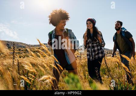 Groupe d'amis heureux randonnées ensemble sur une journée d'été. Groupe d'amis sur marche à travers la campagne. Banque D'Images