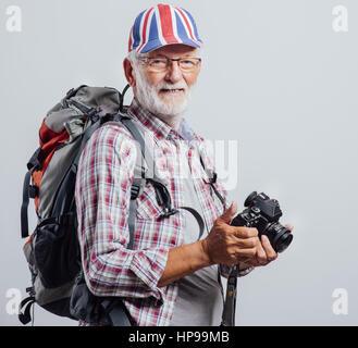 L'explorateur principal holding sac à dos avec un appareil photo numérique, il porte un drapeau britannique cap Banque D'Images