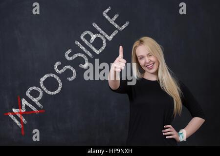 """Une jeune femme qui a fait le mot 'possible' dans le mot """"impossible"""" écrites au tableau wall Banque D'Images"""