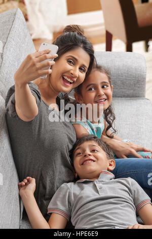 Smiling mother selfies prend avec ses enfants Banque D'Images