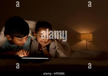 Frère et sœur sharing digital tablet sous couverture dans la nuit dans la chambre Banque D'Images