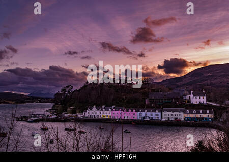 La rangée de maisons colorées sur le quai au port de Portree, Isle of Skye, Scotland. Les rayons du soleil à travers les nuages en couches, avec Cuillin Hills en arrière-plan.