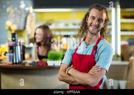 Smiling shop assistant debout dans un magasin de produits de santé avec ses mains croisées Banque D'Images