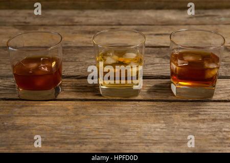 Trois verres de whisky avec Ice Cube sur la table en bois Banque D'Images