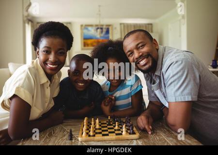 Portrait de famille en jouant aux échecs ensemble à la maison dans la salle de séjour à la maison