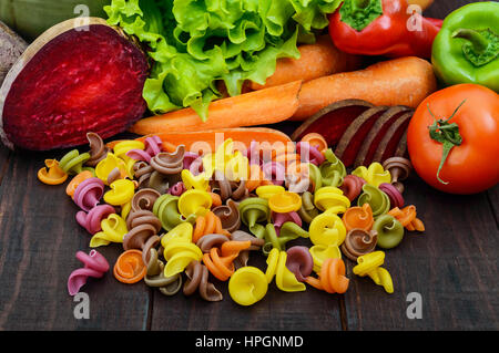 Pâtes colorées sur une table en bois rustique avec des légumes frais (betteraves, verts, carottes, tomates, poivrons). Banque D'Images