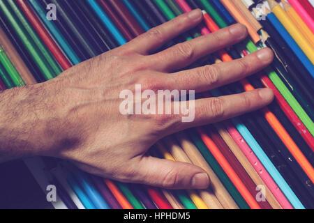 Vue supérieure horizontale, Close up of a woman part touchant un ensemble de plusieurs crayons de couleur Banque D'Images