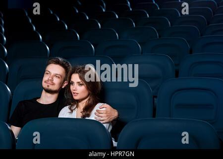 Obtenir tous les romantiques. Beau jeune couple bénéficiant d'un film dans une salle de cinéma vide copyspace Banque D'Images