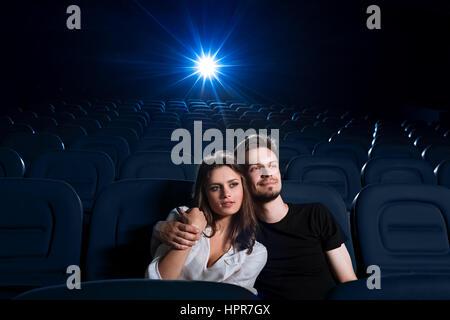 Tellement douillets ensemble. Portrait d'un jeune couple dans l'amour dont la date au cinéma à regarder un film Banque D'Images