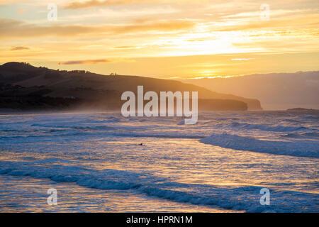 Dunedin, Otago, Nouvelle-Zélande. Surfer sur la pagaie pour monter les vagues de l'océan Pacifique au large de la Banque D'Images