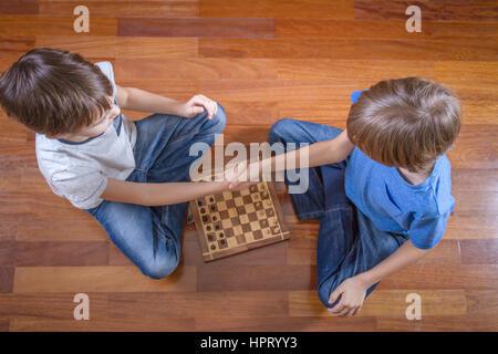 Les enfants se serrer la main avant le jeu d'échecs assis sur un plancher en bois. Jeu, éducation, loisirs concept. Banque D'Images