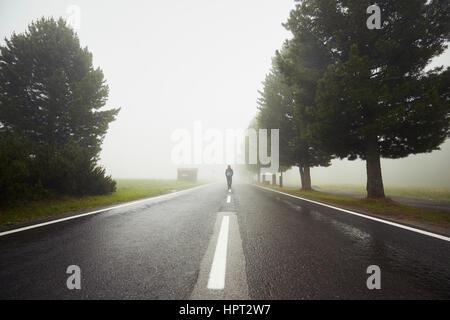 Homme seul marche dans le brouillard mystérieux Banque D'Images