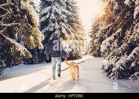 Voyage en hiver la nature. Jeune homme dans des vêtements chauds marche avec son labrador dans la forêt enneigée. Banque D'Images