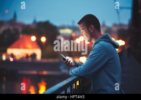 Seul dans la ville nocturne avec téléphone mobile. Bel homme de rêve message Lecture (ou à la recherche sur la vidéo) Banque D'Images