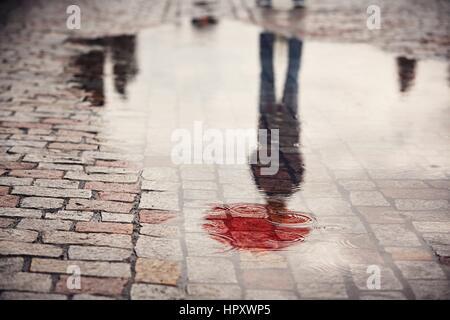 Jour de pluie. Reflet de jeune homme au parapluie rouge dans la flaque d'eau sur la rue de la ville au cours de la pluie.