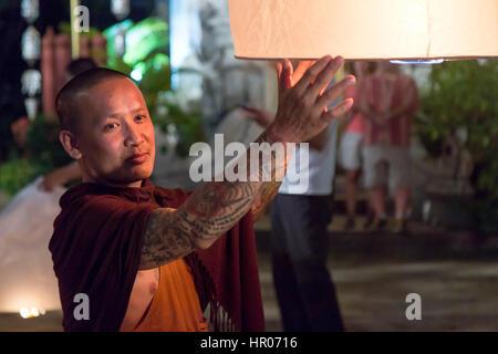 Le moine bouddhiste détient une lanterne flottante traditionnelle avec une bougie dans la nuit. Nuit de fête dans Banque D'Images