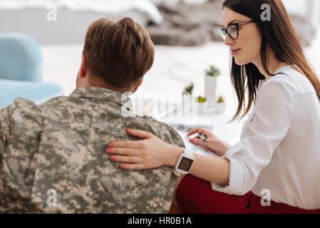 L'interaction avec un patient. Des professionnelles du psychologue heureux assis près de son patient et en mettant Banque D'Images
