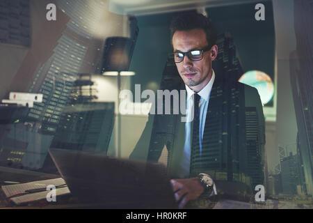 Man concentré au bureau de nuit, grande ville business concept Banque D'Images