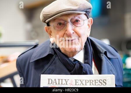 Portrait d'une casquette wearing white vieil homme tenant une copie du Daily Express, un lecteur de journaux retraité Banque D'Images