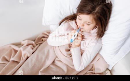 M'aider à récupérer. Agréable petite fille malade au lit et mesure de la température tout en se reposant à la maison Banque D'Images