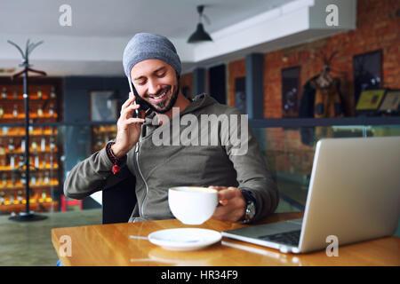 Beau jeune homme hipster avec barbe, assis dans un café à parler téléphone mobile, holding tasse de café et le sourire. Banque D'Images