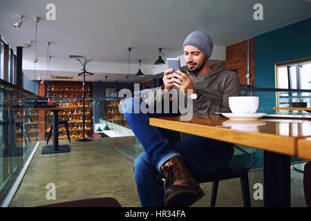 Beau jeune mec avec barbe hippie des sms avec son téléphone portable au bar et d'un cappuccino. Banque D'Images