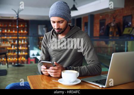 Beau jeune homme hipster au restaurant à l'aide d'un téléphone mobile. Banque D'Images