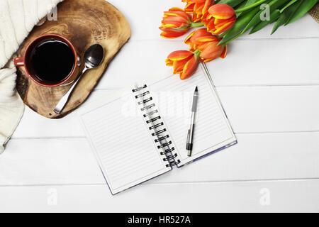 Passage tourné une tasse de café, à livre ouvert, tricoter jeter couverture et un bouquet de fleurs tulipe jaune Banque D'Images