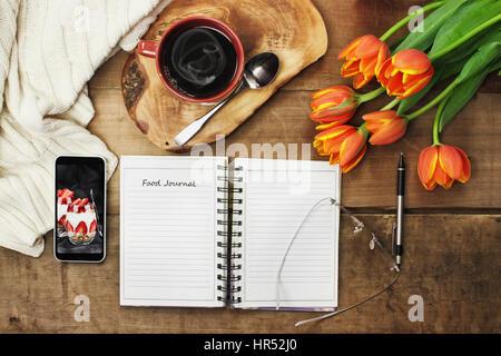 Coup de frais généraux d'un journal alimentaire livre avec téléphone cellulaire, de café et de fleurs sur une table Banque D'Images