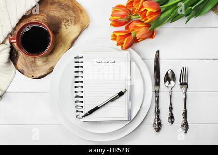 Passage tiré d'un journal alimentaire sur assiettes vides avec une tasse de café et un bouquet de fleurs tulipe Banque D'Images