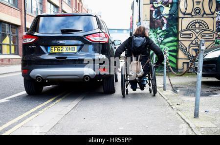 Utilisateur de fauteuil roulant a du mal à passer par mal voiture en stationnement sur la chaussée et double lignes Banque D'Images