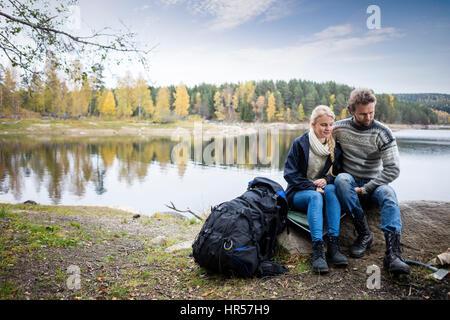 Toute la longueur du jeune couple avec sac à dos de randonnée détente sur Lakeshore pendant camping Banque D'Images