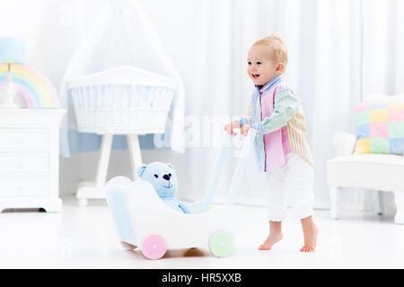 Bébé garçon l'apprentissage de la marche avec du pousser walker en chambre blanche avec des couleurs arc-en-ciel pastel jouets. Jouet pour enfant Aide Premiers pas. Balades pour enfants tout-petits