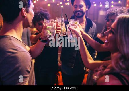 Groupe de jeunes amis au club with cocktails. Les jeunes hommes et femmes à discothèque fête avec des boissons. Banque D'Images