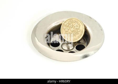Seul British Pound Coin resting in a silver plughole avec gouttelettes d'eau sur le coin et blanc céramique Banque D'Images