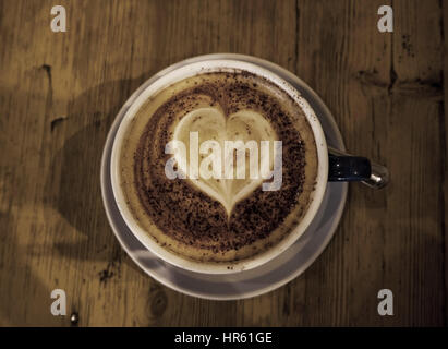 Tasse de café sur une table en bois, pris de dessus, la mousse en forme de coeur sur le dessus de la tonalité des Banque D'Images