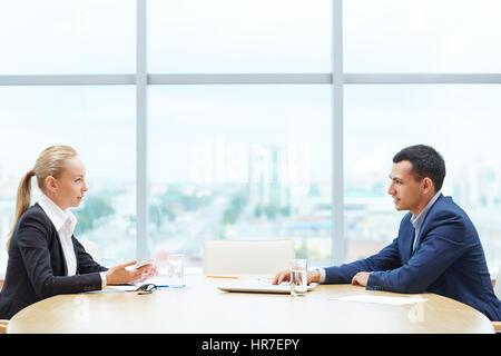 Voir le profil de deux hommes d'affaires, l'homme et de la femme, représentant les parties du contrat, assis en face de l'autre à table pour discuter au cours de répondre