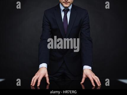 Closeup portrait of méconnaissable d'autorité portant tailleur debout appuyée sur table dans de puissants posent Banque D'Images