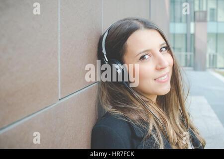 Jeune femme d'affaires authentique se détend en écoutant de la musique dans la ville Banque D'Images