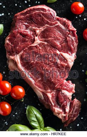 Fresh steak aux épices, tomates et feuilles de basilic sur en arrière-plan. La viande non cuite. Copier l'espace. Banque D'Images