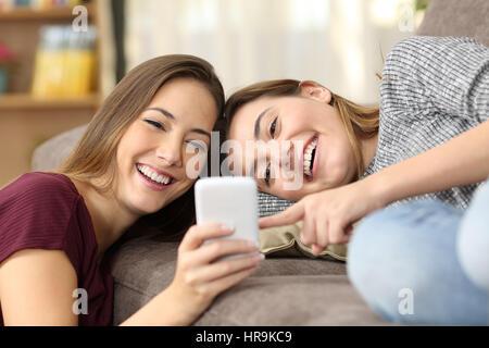Colocation heureux d'avoir l'oeil sur le contenu en ligne dans un téléphone intelligent allongé sur un canapé dans Banque D'Images