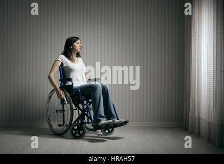 Femme triste assis sur fauteuil roulant dans la salle vide Banque D'Images
