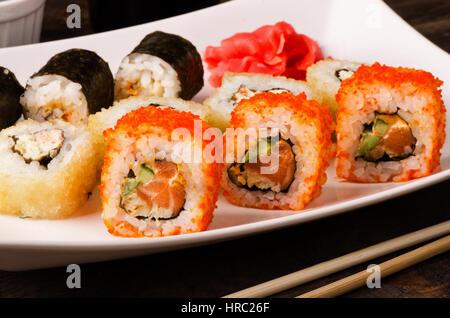 Ensemble rouleau de sushi différents en Californie, avec le saumon et les crevettes tempura sur une plaque Banque D'Images