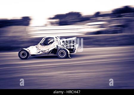 Voiture de course de Buggy sur la grande vitesse, tourné sur le côté avec effet de flou et de saturation faible Banque D'Images