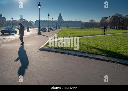 Personne phone jette un long hiver ombre portée avec les invalides dans l'arrière-plan, Paris, France. Banque D'Images