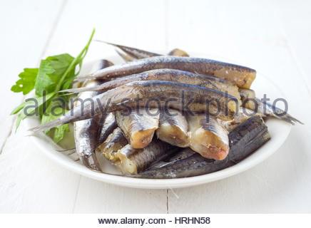 Tas de matières de sardines sur la plaque avec le persil sur sol en bois Banque D'Images